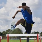 Man Jumping Hurdles On A Track